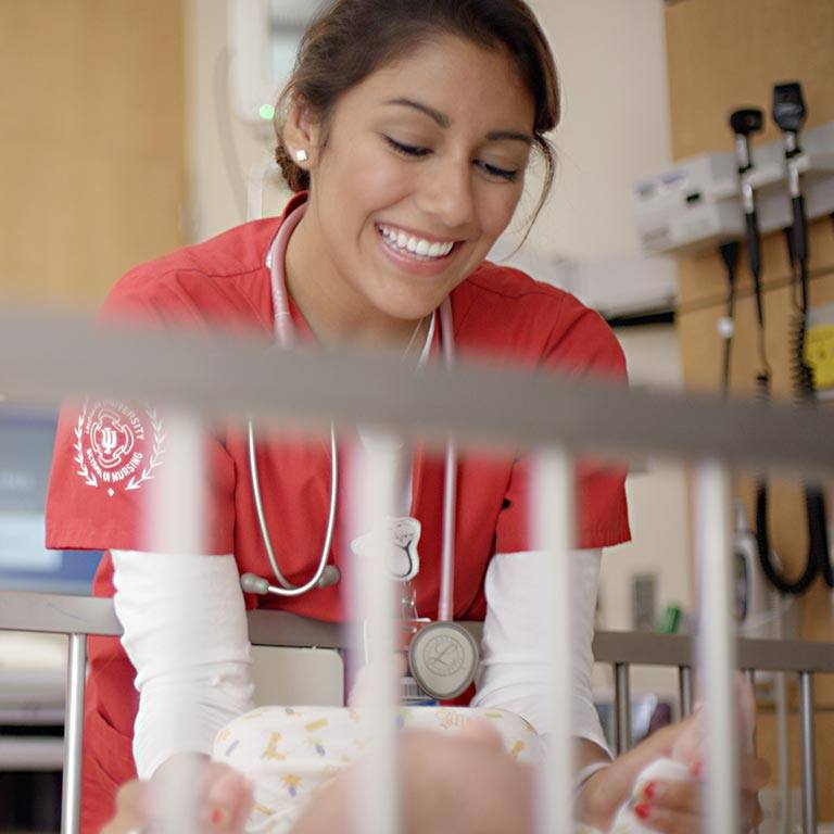A nurse in red scrubs leans over the edge of a crib to play with a baby.