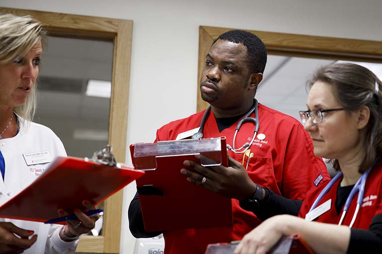Male and female nursing students in red scrubs talking to a female preceptor at a hospital in a white coat.